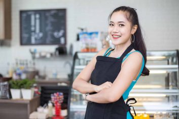 Asian barista woman standing for present cafe with attractive smiling at front of coffee shop. Woman with owner business concept.